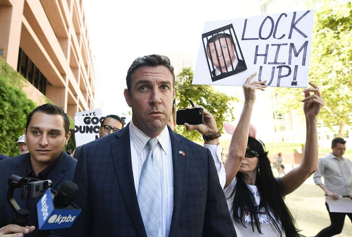 FILE - In this July 1, 2019, file photo, U.S. Rep. Duncan Hunter, R-Calif., center, leaves federal court after a hearing in San Diego. A judge is expected to rule on a bid by Hunter to move his trial on charges that he looted campaign funds for personal use and even to dismiss the charges outright. U.S. District Judge Thomas Whelan in San Diego decided a flurry of pretrial motions last week but deferred some decisions until Monday, July 8 to consider filings that arrived too late for him to read. (AP Photo/Denis Poroy, File)