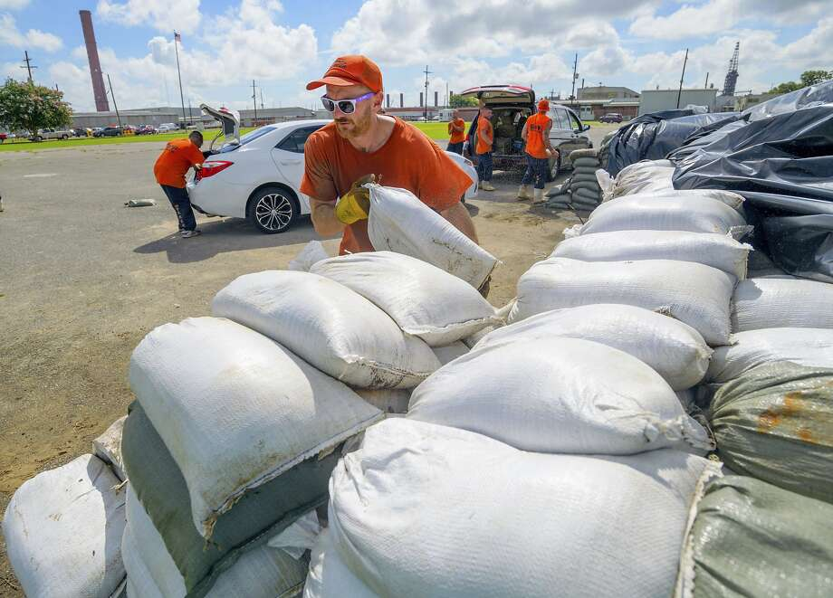 An inmate of the St. Bernard Parish Sheriff's Office moves sandbags in Chalmette, ahead of Tropical Storm Barry. As much as 20 inches of rain could fall in parts of eastern Louisiana. Photo: Matthew Hinton / Associated Press