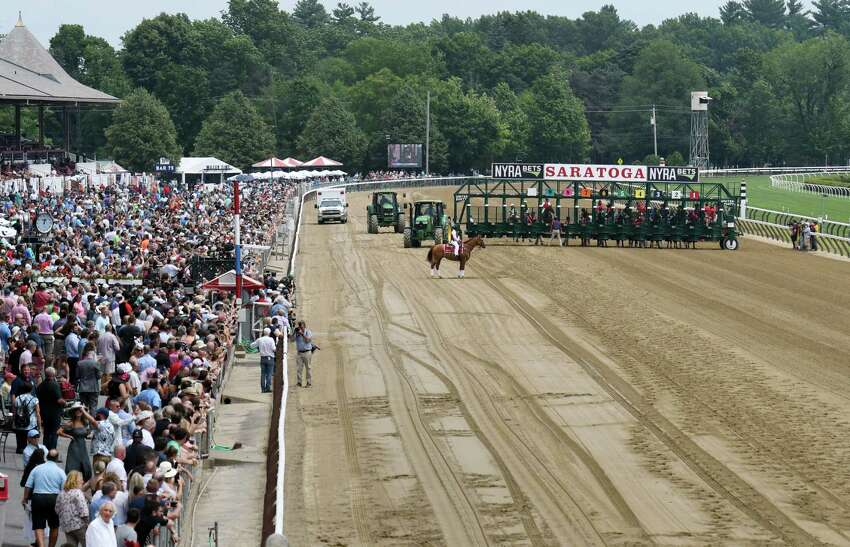 Attendees gather near the track before post time during opening day at the track on Thursday, July 11, 2019 at Saratoga Race Course in Saratoga Springs, NY. (Phoebe Sheehan/Times Union)