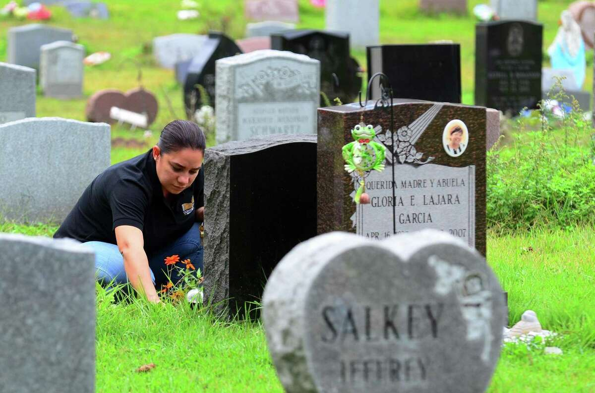 A woman who wished not to give her name, checks on a family member's grave at Park Cemetery in Bridgeport, Conn., on Wednesday, Oct. 3, 2018. It is believed that some older graves and grave markers in the cemetery have been moved in effort to make way for newer burials.