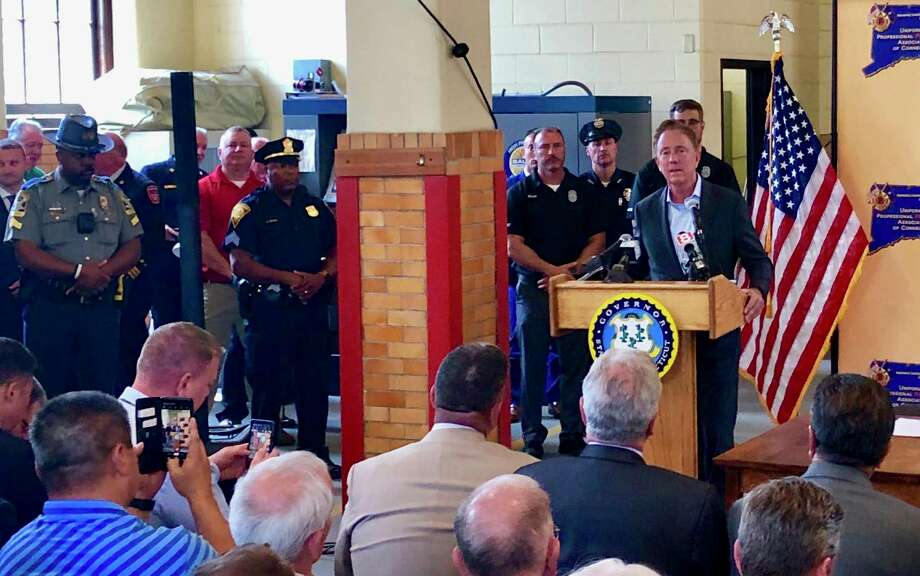 Gov Ned Lamont holds a bill signing ceremony at Engine 10 of the Waterbury Fire Department on June 10 to commemorate the adoption of a state law that will provide workers' compensation benefits to police officers, parole officers, and firefighters who have been diagnosed with post-traumatic stress disorder after witnessing an unnerving event in the line of duty. Photo: Contributed