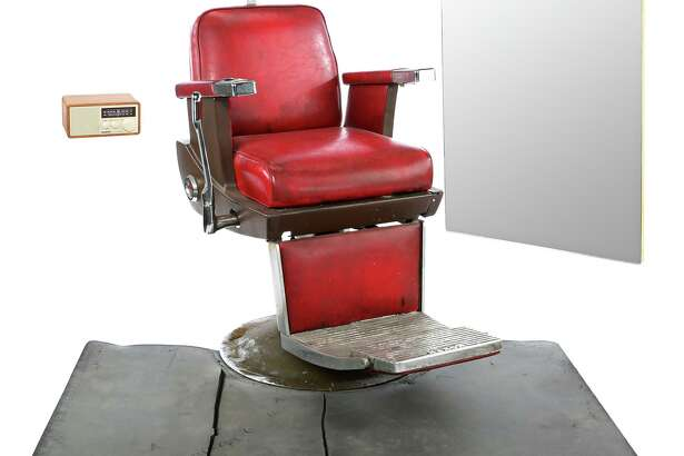 """Pop's Barber Shop Chair and Accessories """"Pop's Barber Shop chair and accessories from Season 1 of Marvel's Luke Cage. Customers getting haircuts from Pop sit in Pop's classic barber chairs, which are later replaced after Pop's death, throughout the season. This red leatherette barber chair, complete with armrests, a footrest, and a padded headrest, features metal and brown plastic components, as well as a gray anti-fatigue floor mat, a large wood-backed mirror, and a white AM/FM radio with a brown wood case."""""""