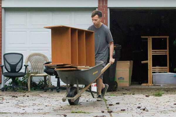 Brandon Tanner helps move damaged furniture from a friend's home in the Elm Grove Village subdivision, Friday, May 10, 2019, in Kingwood. Flash flooding caused several home in the neighborhood to take in water.