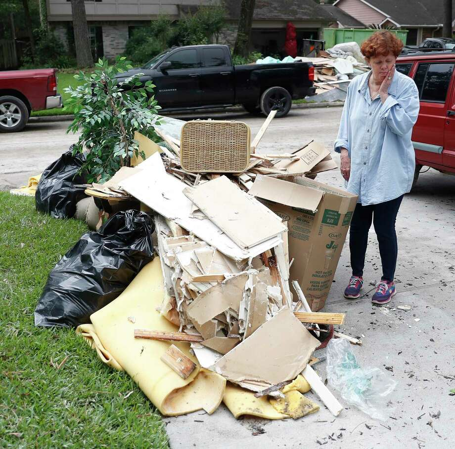 Sharon Schoeneck reacts as she looks at a growing stack of her belongings sits on the curb of her and her husband, David's home, as she and other residents in the Elm Grove subdivision, in Kingwood, cleaned up, May 9, after floodwaters damaged their homes earlier in the week. Photo: Karen Warren, Houston Chronicle / Staff Photographer / © 2019 Houston Chronicle