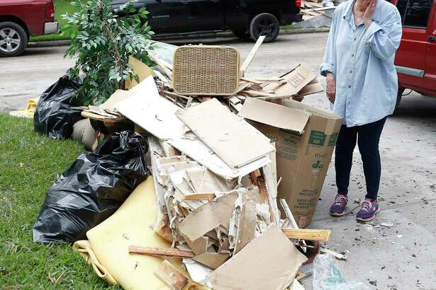 Sharon Schoeneck reacts as she looks at a growing stack of her belongings sits on the curb of her and her husband, David's home, as she and other residents in the Elm Grove subdivision, in Kingwood, cleaned up, Thursday, May 9, 2019, after floodwaters damaged their homes Tuesday and Wednesday.