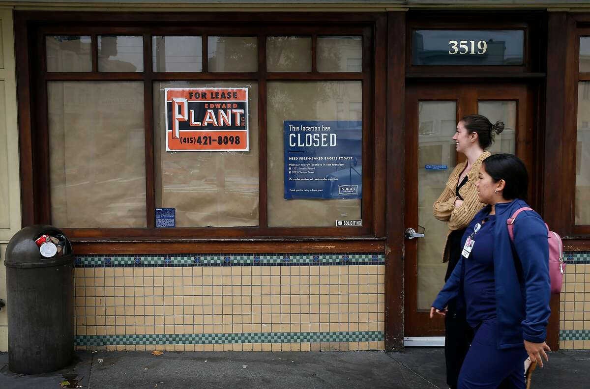 Pedestrians stroll past the vacant storefront where Noah's Bagels was located in the Laurel Village shopping district in San Francisco, Calif. on Thursday, July 11, 2019. Several businesses along the strip on California Street have suddenly shut their doors for good.