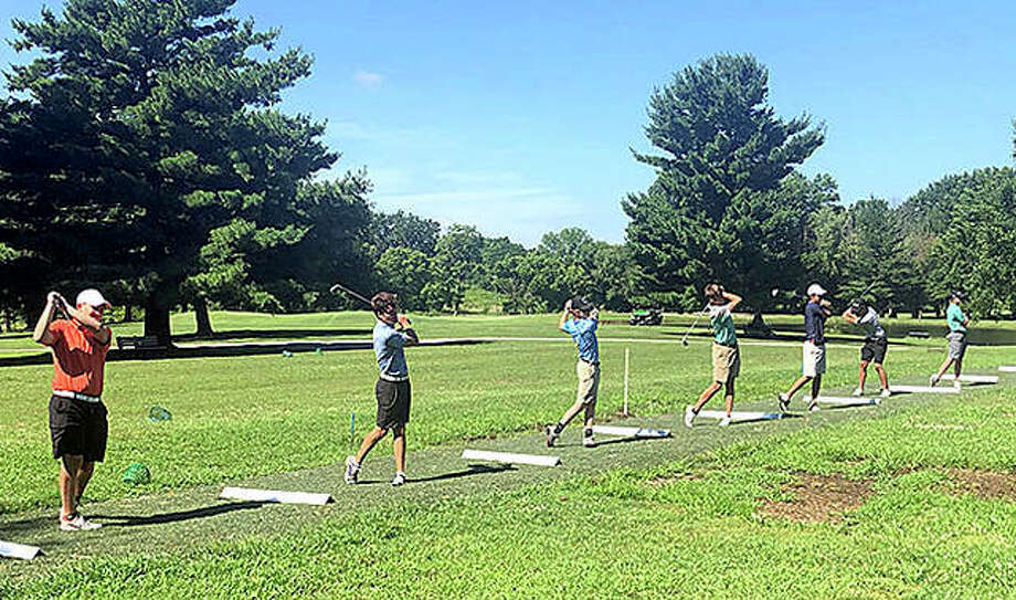 Members of the Edwardsville boys' golf team practice Thursday morning on the driving range at Oak Brook Golf Club. Photo: Scott Marion/The Intelligencer