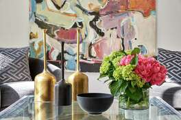 Though the furnishings are gray, art provides lots of color in the room.
