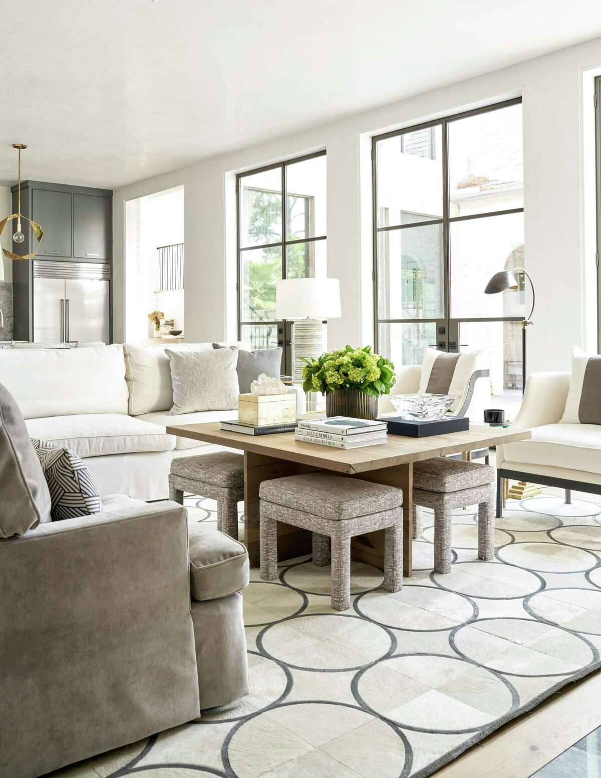 Furniture in creams and taupes sits on a cowhide rug pieced into a geometric design.