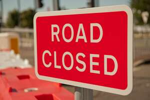 Close up of a red & white ROAD CLOSED sign.
