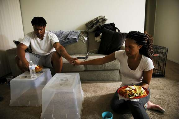 LaRance Braggs, 39, prays with his wife Lanise, 40, as they bless their taco dinner in their apartment in Tracy, Calif., on Tuesday, July 9, 2019. The couple has been married since July 30, 2017. A month ago they were homeless and living in their car on MLK Jr. Way in West Oakland.   �She�s been supportive through everything. She�s my backbone when I need a backbone,� LaRance said of Lanise. �She just kept telling me to don�t give up. She knew it was going to work out better.�   With help from Bay Area organization Swords to Plowshares, a program for military veterans, Braggs was recently hired as a supervisor for Mint Security, Inc., a private security company based in San Francisco.