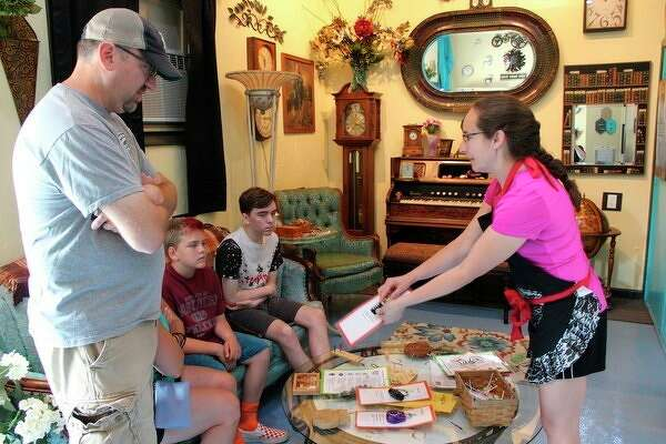 Conundrums co-owner Rikkii Clarent teaches a family how escape rooms work. The Port Austin-based escape room opened earlier this month and offers entertainment for all ages. (Robert Creenan/Huron Daily Tribune)