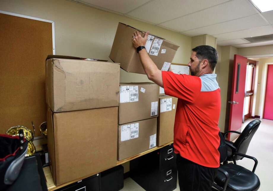 Bridge City head football coach Allen Deshazo puts new uniforms on desks and shelfs in an effort to protect them any possible water damage Thursday at Bridge City's high school. Photo taken on Thursday, 07/11/19. Ryan Welch/The Enterprise Photo: Ryan Welch, Beuamont Enterprise / The Enterprise / © 2019 Beaumont Enterprise