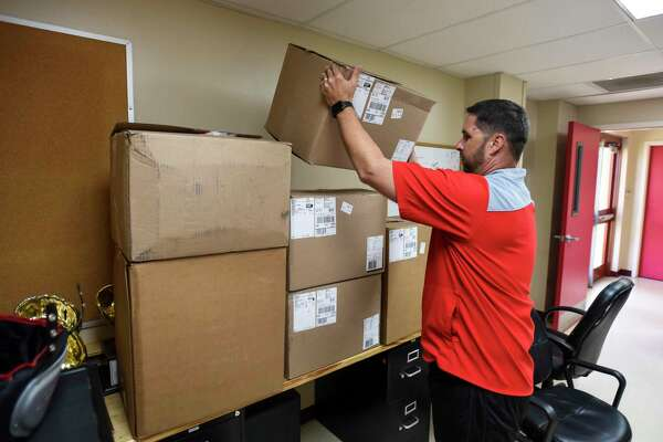Bridge City head football coach Allen Deshazo puts new uniforms on desks and shelfs in an effort to protect them any possible water damage Thursday at Bridge City's high school. Photo taken on Thursday, 07/11/19. Ryan Welch/The Enterprise