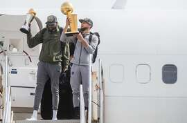 The Golden State Warriors' Stephen Curry carries the NBA Championship trophy while Warriors' Kevin Durant carries his MVP trophy as the team arrives from Cleveland, Ohio at Landmark Aviation in Oakland, Calif. Saturday, June 9, 2018. after defeating the Cleveland Cavaliers in the NBA Finals.