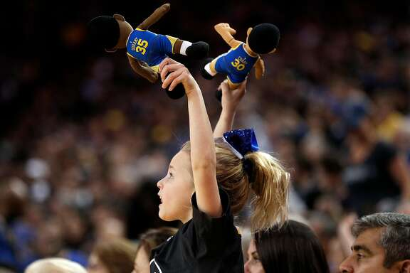 Maddyn Brown, 7, of Pleasanton waves her Stephen Curry and Kevin Durant dolls in the second half as the Golden State Warriors played the Minnesota Timberwolves at Oracle Arena in Oakland, Calif., on Thursday, January 25, 2018.