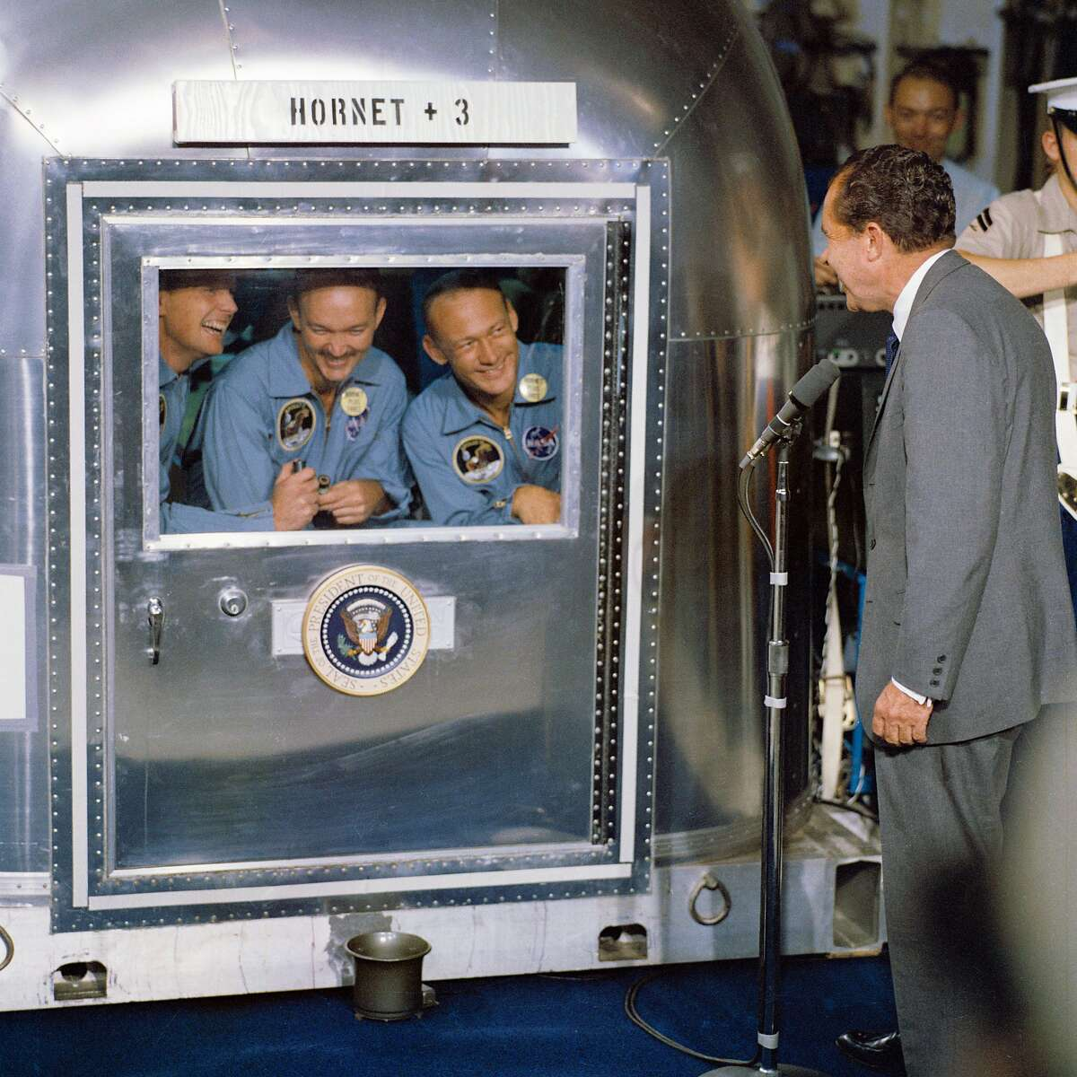 """(24 July 1969) --- United States President Richard M. Nixon was in the central Pacific recovery area to welcome the Apollo 11 astronauts aboard the USS Hornet, prime recovery ship for the historic Apollo 11 lunar landing mission. Already confined to the Mobile Quarantine Facility (MQF) are (left to right) Neil A. Armstrong, commander; Michael Collins, command module pilot; and Edwin E. Aldrin Jr., lunar module pilot. Apollo 11 splashed down at 11:49 a.m. (CDT), July 24, 1969, about 812 nautical miles southwest of Hawaii and only 12 nautical miles from the USS Hornet. The three crewmen will remain in the MQF until they arrive at the Manned Spacecraft Center's (MSC) Lunar Receiving Laboratory (LRL). While astronauts Armstrong and Aldrin descended in the Lunar Module (LM) """"Eagle"""" to explore the Sea of Tranquility region of the moon, astronaut Collins remained with the Command and Service Modules (CSM) """"Columbia"""" in lunar orbit. Photo credit: NASA"""