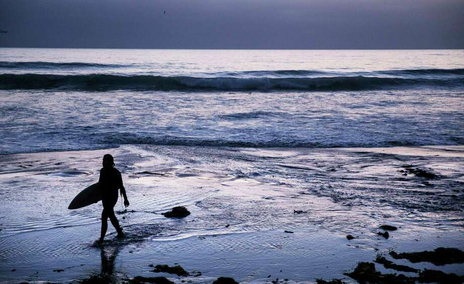 FILE - In this July 2, 2019, file photo a surfer walks out of the water after riding waves at dusk at Scripps Beach in San Diego. With hotel and airline loyalty programs, you can take the sting out of this year's travel costs by leveraging those expenditures to pay for next year's trip. (AP Photo/David Goldman, File) Photo: David Goldman, STF / Associated Press / 2019 Associated Press. All rights reserved.