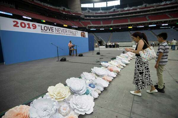 Maria Luisa Castro, right, takes photos of the main stage setup at the International Jehovah's Witnesses Convention at NRG Stadium in Houston, Thursday, July 11, 2019. Nearly 50,000 people are expected to attend the three-day convention from July 12-14.