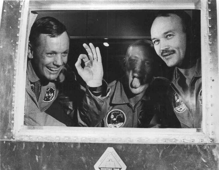 Apollo 11 astronauts looked healthy and happy when they arrived aboard the mobile quarantine facility at Ellington Air Force Base. Neil Armstrong gives the A-OK sign. Buzz Aldrin hams it up for friends as Mike Collins grins.