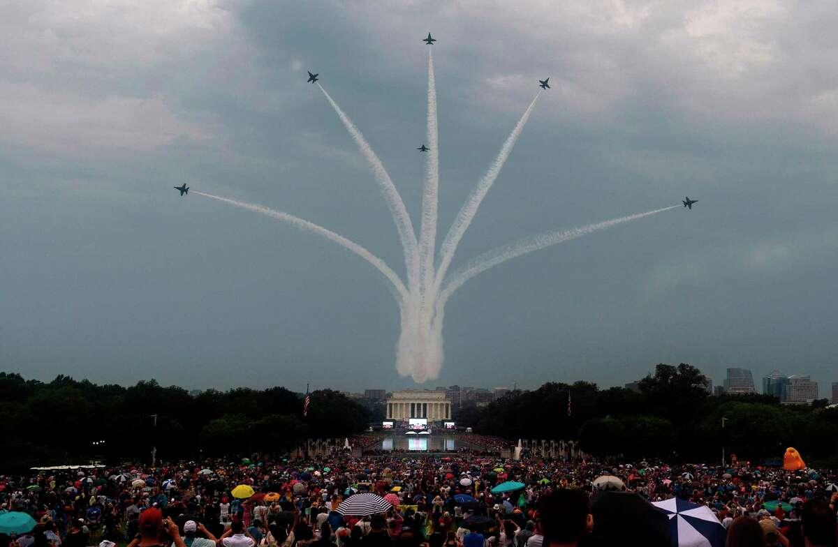 TOPSHOT - The Blue Angels (six F-18s) fly overhead as people gather on the National Mall for the
