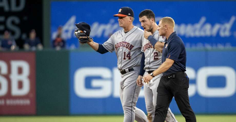 Houston Astros shortstop Alex Bregman (2) is escorted off the field by manager A. J. Hinch (14) and a trainer after taking a ground ball by Texas Rangers' Shin-Soo Choo to the face during the third inning of a baseball game Thursday, July 11, 2019, in Arlington, Texas. Bregman was replaced at shortstop by Myles Straw. (AP Photo/Jeffrey McWhorter) Photo: Jeffrey McWhorter/Associated Press