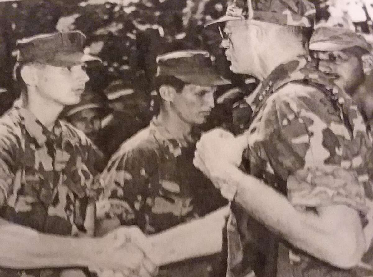 Cpl.Jim Spain of Troy shakes hands with Gen. Leonard F Chapman, commandant of the Marine Corps in Vietnam, who visited several units in August 1969, a month after the moon landing. Spain recalls that after receiving a coded message, he pointed skyward and told his American squad and their counterparts in a Vietnamese militia that U.S. astronauts had just landed on the moon. (Courtesy Jim Spain)