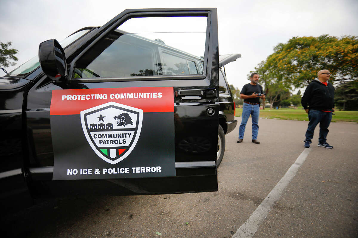 Members of Union del Barrio San Diego stand outside one of the vehicles they used to drive the streets in and around the Shelltown neighborhood on July 4, 2019. The volunteer community organization was looking for activity by Immigration and Customs Enforcement agents, documenting it, when they find it, and informing the community.