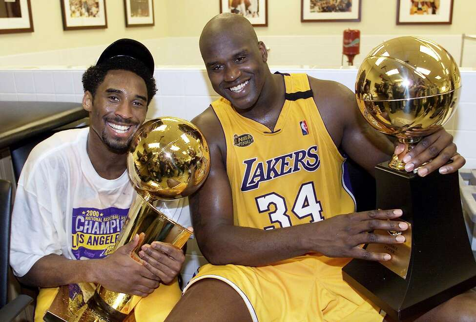 Kobe Bryant of the Los Angeles Lakers holds the Larry O'Brien trophy as teammate Shaquille O'Neal holds the MVP trophy after winning the NBA Championship against Indiana Pacers in 2000.