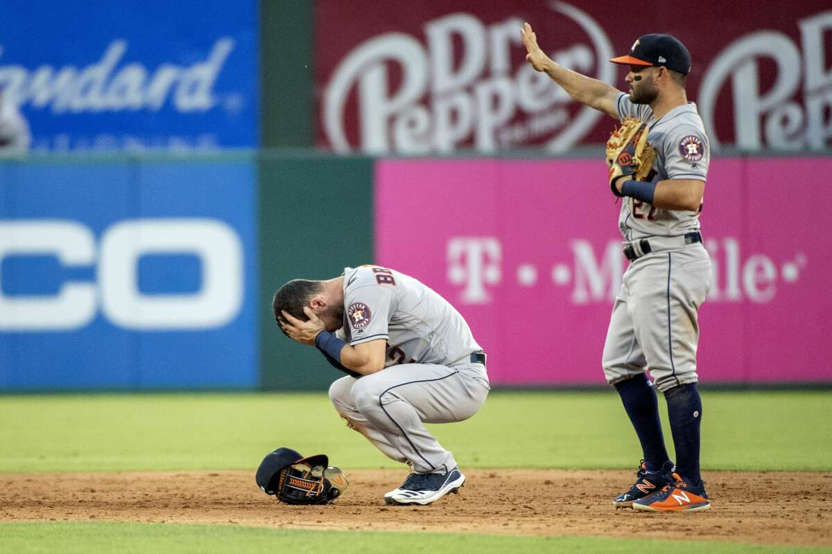 Houston Astros shortstop Alex Bregman reacts to being hit in the face by a ground ball by Texas Rangers' Shin-Soo Choo as second baseman Jose Altuve (27) calls for time during the third inning of a baseball game Thursday, July 11, 2019, in Arlington, Texas. Bregman left the game because of the injury. (AP Photo/Jeffrey McWhorter)