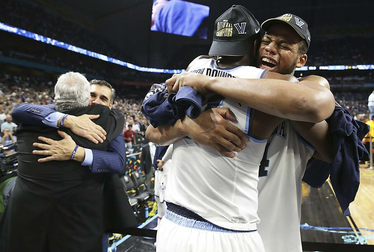 Coach Jay Wright and forward Omari Spellman get some hugs in celebration after winning in the final game of the NCAA National Basketball Championships at the Alamodome on April 2, 2018.