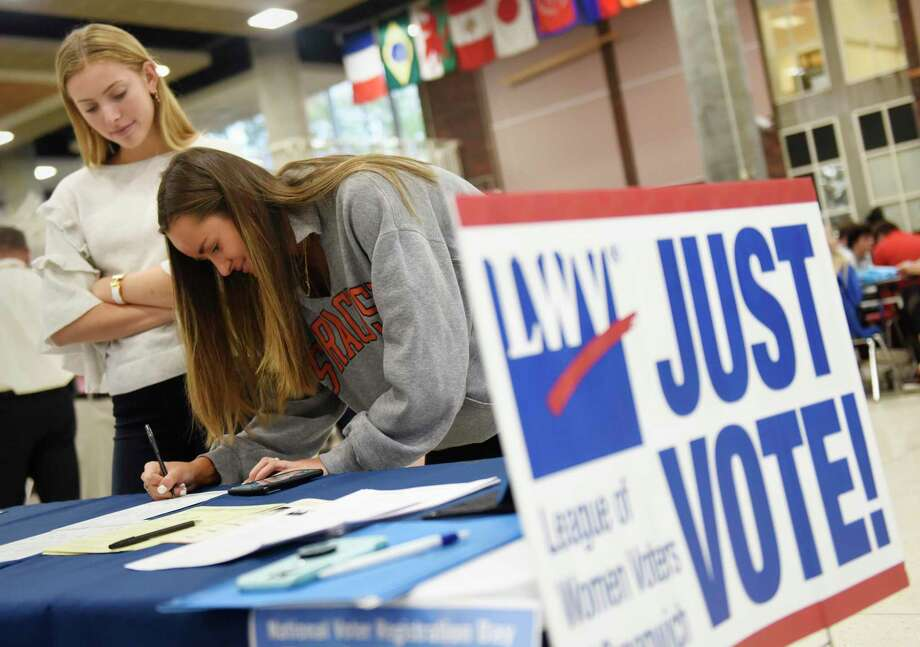 GHS senior Karolina Bertulis signs up to vote accompanied by fellow senior Jane Cameron at the League of Women Voters of Greenwich voting sign-up station at Greenwich High School in Greenwich, Conn. Tuesday, Sept. 25, 2018. The LWV set up a stand in the student center during the lunch periods in an nonpartisan effort to register eligible students to vote in the upcoming election. Photo: File / Tyler Sizemore / Hearst Connecticut Media / Greenwich Time