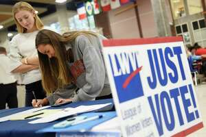 GHS senior Karolina Bertulis signs up to vote accompanied by fellow senior Jane Cameron at the League of Women Voters of Greenwich voting sign-up station at Greenwich High School in Greenwich, Conn. Tuesday, Sept. 25, 2018. The LWV set up a stand in the student center during the lunch periods in an nonpartisan effort to register eligible students to vote in the upcoming election.