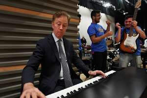 Gov. Ned Lamont hops on the keyboards for an impromptu jam with the Harding High School Rock Band during a visit to the school in Bridgeport, Conn. on Tuesday, March 26, 2019.