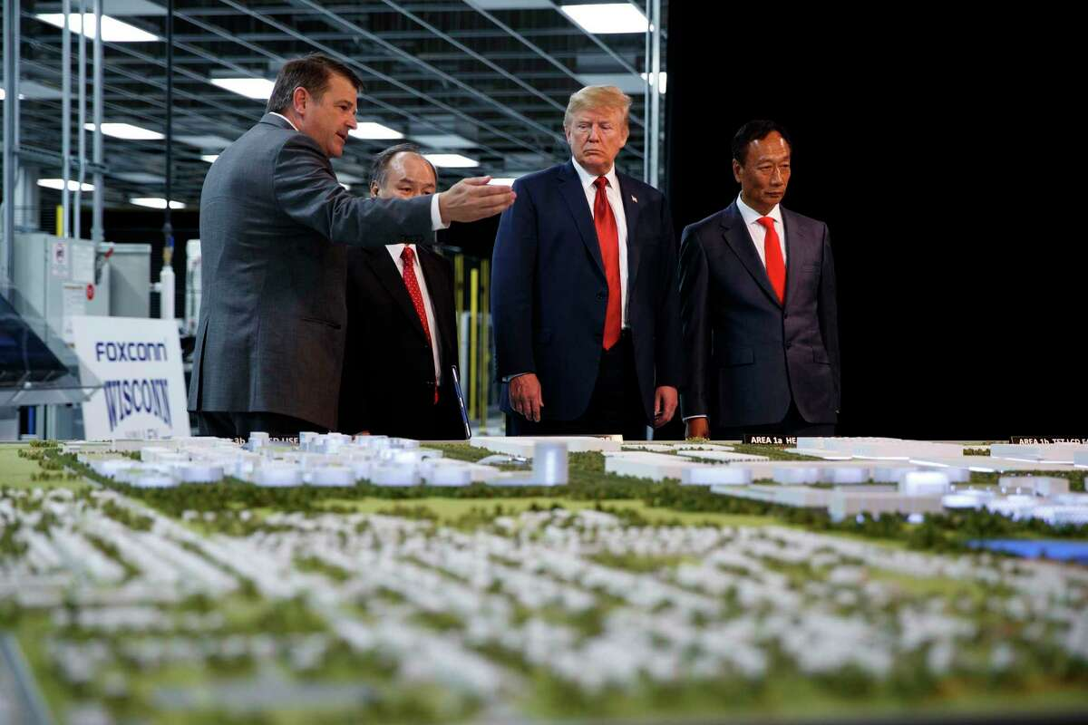 President Donald Trump takes a tour of Foxconn with Foxconn chairman Terry Gou, right, and CEO of SoftBank Masayoshi Son in Mt. Pleasant, Wis., last year. Wisconsin promised Foxconn over $4 billion in incentives to build a high-tech facility that is supposed to create 13,000 jobs. But since the 2017 announcement, the company has failed to meet job targets and downgraded the type of facility it plans to build.