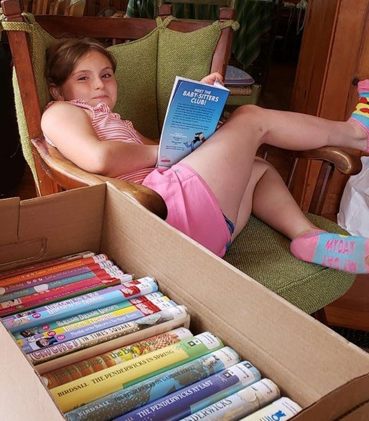 Ann-Marie Helldorfer's niece, Annaliese Cooney, with some of the books Ann-Marie put together for a summer reading collection. (Provided)