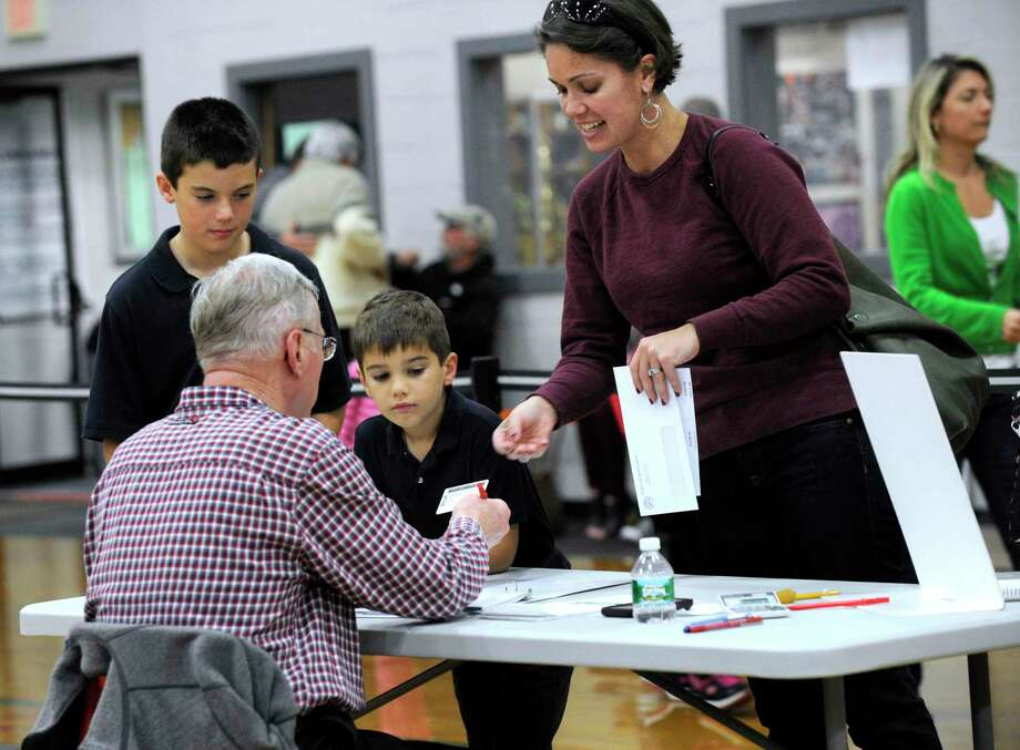 Joy Strand, with sons Joel, 9, and Jackson, 6, check in with official checker Doug Kleinmann at the Yanity Gym polling place Tuesday afternoon. The Yanity Gym, the district 3 polling place in Ridgefield, Conn. had a steady stream of voters Election Day, Nov. 4, 2014. Photo: Carol Kaliff / Carol Kaliff / The News-Times