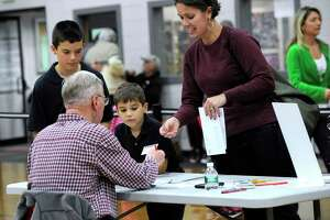 Joy Strand, with sons Joel, 9, and Jackson, 6, check in with official checker Doug Kleinmann at the Yanity Gym polling place Tuesday afternoon. The Yanity Gym, the district 3 polling place in Ridgefield, Conn. had a steady stream of voters Election Day, Nov. 4, 2014.