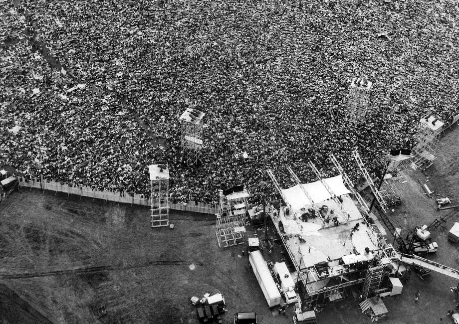 In this Aug. 16, 1969 file aerial photo, music fans pack around the stage at the original Woodstock Music and Arts Festival, lower right, in Bethel, N.Y. The Bethel Woods Center for the Arts, a concert venue built on the original Woodstock site, announced Thursday, Dec. 27, 2018, that it will host the 50th anniversary of the historic event at the original Woodstock concert site on Aug. 16-18, 2019. (AP Photo/Marty Lederhandler, File) Photo: Marty Lederhandler / Associated Press / Copyright 1969, 2018 The Associated Press. All rights reserved