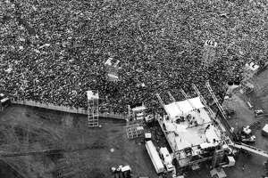 In this Aug. 16, 1969 file aerial photo, music fans pack around the stage at the original Woodstock Music and Arts Festival, lower right, in Bethel, N.Y. The Bethel Woods Center for the Arts, a concert venue built on the original Woodstock site, announced Thursday, Dec. 27, 2018, that it will host the 50th anniversary of the historic event at the original Woodstock concert site on Aug. 16-18, 2019. (AP Photo/Marty Lederhandler, File)