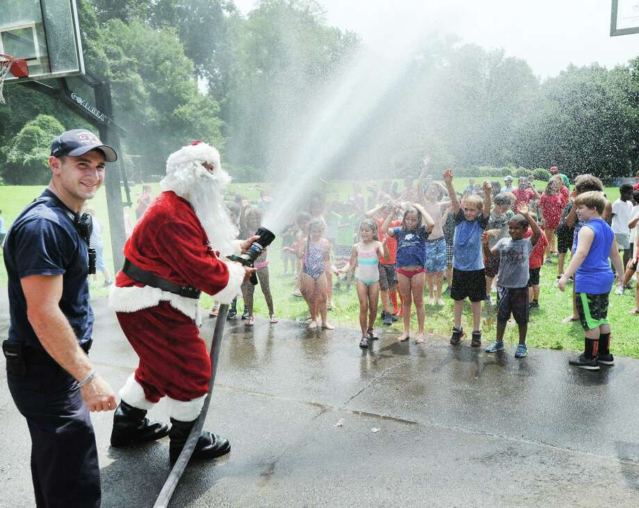 With a blast of water from a hose, Santa cools off campers during the annual Boys & Girls Club of Greenwich Christmas in July event, courtesy of the Greenwich Fire Department, at Camp Simmons, Greenwich, Conn., Friday, July 27, 2018. Photo: Bob Luckey Jr. / Hearst Connecticut Media / Greenwich Time