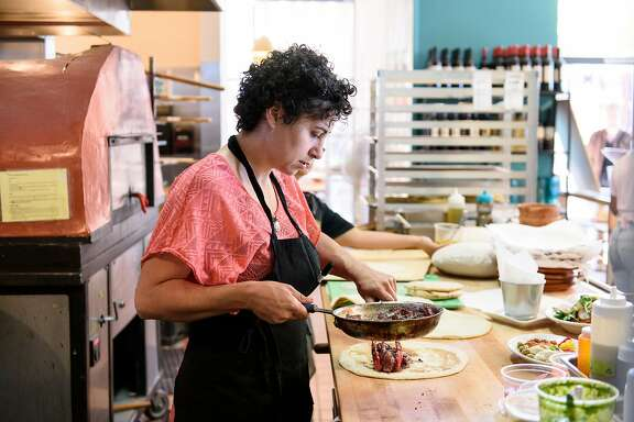 Owner Reem Assil works in the kitchen during lunch at Reem's in Oakland, Calif, on Wednesday, April 17, 2019.