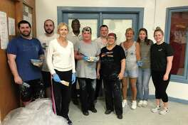 """35 FOR 35: Burzenski & Co., an East Haven accounting, tax and financial services firm, continues to celebrate its 35th anniversary with a """"35 for 35"""" campaign in which members complete projects for area nonprofits. The latest venture was a large painting project at Immanuel Baptist Shelter in New Haven, where staff members painted one very large room and two small rooms. From left are Jared Poltrak, Dom Musto, Mary Murphy, shelter Executive Director Aaron Haley, Kathleen Hunt, Paul Falzone, Gail Cable, Becky Cagley, Eugenia Borta and Kim Purisky."""