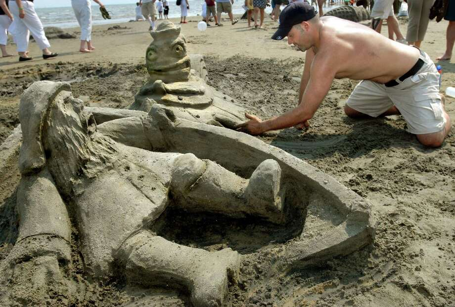 "Brad Connent, of West Haven, works on his sand sculpture, ""A Reel Fishy Story,"" which was voted best entry at an earlier Milford Sand Sculpture Competition. The 42nd annual event returns to Walnut Beach July 27. Photo: Melanie Stengel / Hearst Connecticut Media File Photo"