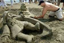 """Brad Connent, of West Haven, works on his sand sculpture, """"A Reel Fishy Story,"""" which was voted best entry at an earlier Milford Sand Sculpture Competition. The 42nd annual event returns to Walnut Beach July 27."""