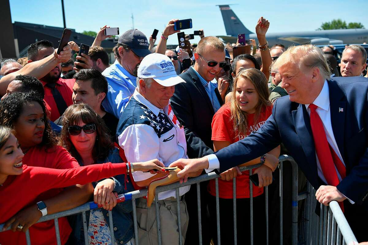 US President Donald Trump holds a shoe for signing as he greets supporters after steping off Air Force One upon arrival at General Mitchell International Airport in Milwaukee, Wisconsin on July 12, 2019. - Trump will be in Milwaukee to visit an aerospace company and attend a fundraiser. (Photo by MANDEL NGAN / AFP)MANDEL NGAN/AFP/Getty Images