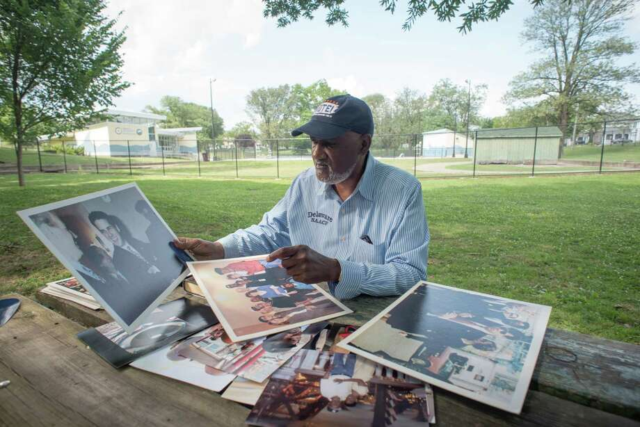"Richard ""Mouse"" Smith looks at photos showing his work as a civil rights leader and his decades-long friendship with Joe Biden near the pool in Wilmington, Delaware, where he and the former vice president met as young men. Photo: Photo For The Washington Post By André Chung / André Chung"