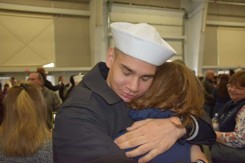 Macoy Hicks hugs his younger sister Sienna Hicks after graduating from Navy boot camp.