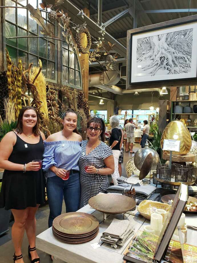 """From left, Caroline, Madeline and Lisa Parelli Gray attend """"The Forest Floor"""" fine arts exhibit at Terrain on July 11, 2019, sponsored by Terrain and the Artists Collective of Westport. The trio stand next to art by Dan Long, a Staples diving coach and longtime Westporter who passed away in May. Photo: Liana Teixeira / Hearst Connecticut Media"""
