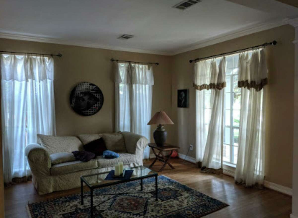 """Before: A """"before"""" photo of the formal living room -- not enough furniture and inadequate window treatments."""
